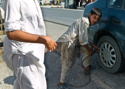 A young boy working at a service station adds air to the tires of a client.