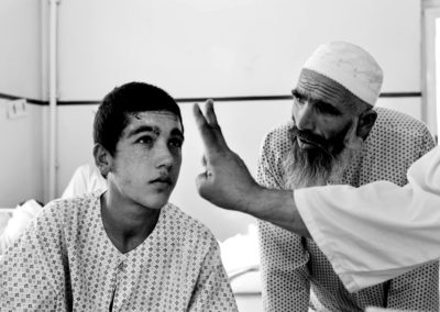 A doctor tests Mohammad Omer's vision as the patient's father looks on.