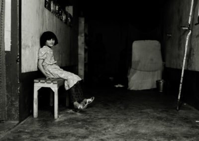 A young girls sits in the hallway of the prison.
