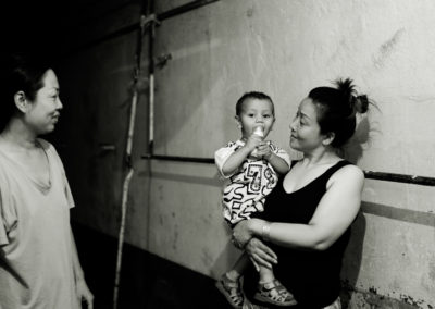 Chinese women accused of prostitution play with another inmate's child.