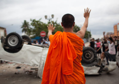 July 28, 2013. Phnom Penh, Cambodia. A monk gestures to rioters after a dispute at the polls in Phnom Penh's Stung Meanchey district.