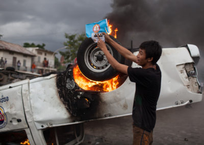 A youth holds up a ruling CPP party sign in front of a torched government vehicle at the scene of riots following a dispute at the polls.