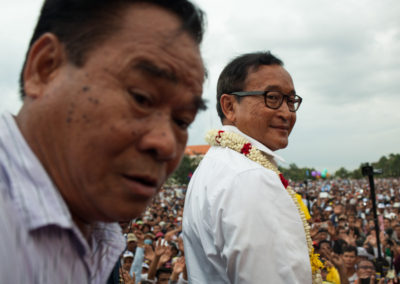 Sam Rainsy turns back an instant before addressing a huge crowd of supporters in the capital one week after the elections.