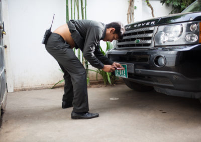 A body guard attaches the national assembly plates to opposition  Sam Rainsy's car on election day at CNRP HQ before he and his wife head out to the polls.