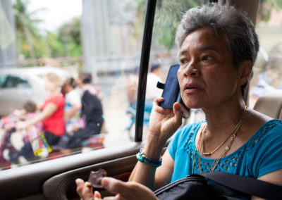 Sam Rainsy's wife, Toulong Samoura, talks on the phone while driving to the polls on election day.