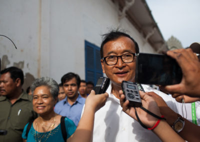 Sam Rainsy and his wife, Toulong Samoura, arrive at a polling station to greet supporters. Samoura was allowed to vote, but her husband was barred from casting his ballot by the ruling party.