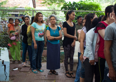 Opposition party leader Sam Rainsy's wife, Toulong Samoura, stands in line to vote at a polling station in Phnom Penh.