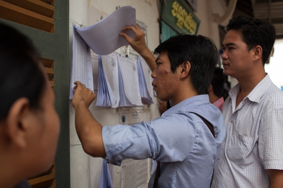 Voters check registration lists at a polling station in Phnom Penh.