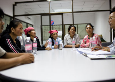 nion leaders gather around a table at a garment factory on the outskirts of Phnom Penh to discuss their working conditions with Ork Sam Ol (right), a monitor for the ILO's Better Factories Cambodia.