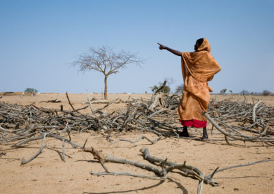 A Sudanese refugee points in the direction of a truck delivering more firewood to camp Iridimi.