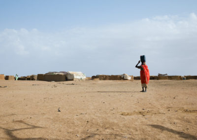 A Sudanese refugee makes her way back to her home after getting water from the well inside camp Iridimi.