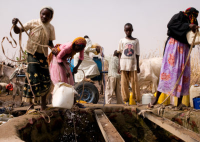 Locals collect water from a well built by German NGO Help.