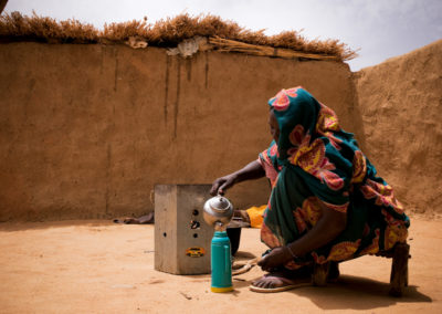 "A Darfuri refugee uses a ""Save 80 Stove"" to make tea, a stove that economizes 80% of the wood used."