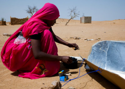A Darfuri refugee uses a solar stove to boil water in order to save firewood.