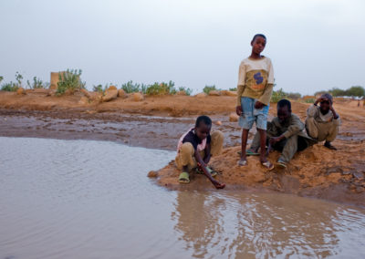 Young boys play with water recently accumulated in the wadi (dry river beds) as the rainy season approaches.