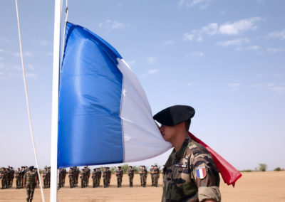 Soldiers of the 7eme Battallion de Chasseurs Alpins stand for the raising of the flag at Camp Farchana during July 14 celebrations.