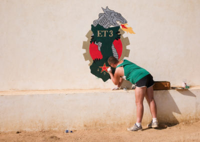 A soldier paints the regiment's coat of arms on a wall at the base in Iriba.