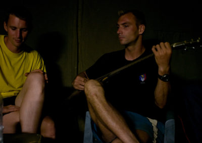 Corporal Chef M. Bouland (right) plays the guitar for his fellow soldiers during nighttime relaxation hours.