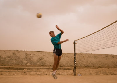 Soldiers play volleyball during a sandstorm.