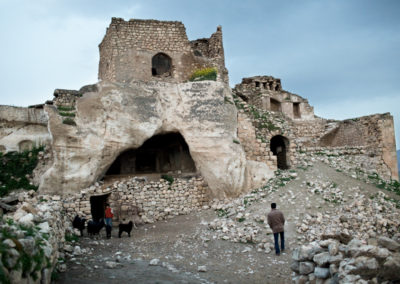 Erkhan walks up the hill of an ancient cave dwelling in Hasanakeyf still used by locals as a shed for their livestock.
