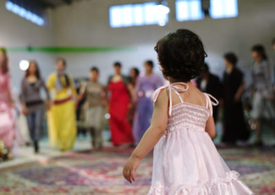 May 3, 2007. Urmia, Iran. A young girl looks on as women perform traditional Kurdish dancing at a wedding celebration in Urmia.