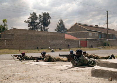 GSU units take aim down a street in Nakuru during clashes between rival groups.