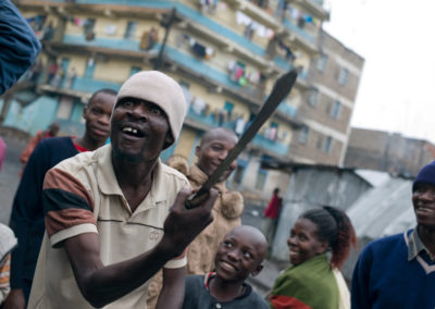 A resident of Mathare North slum brandishes a machete while talking to a crowd about protecting the community, after participating in the lynching of a suspected informant.