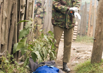 Police come to collect the body of a Kikuyu boy who was slashed with a machete in the Nakuru slum of Idima.