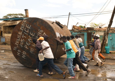 Youths push an oil barrel through the streets of Kibera slum to set up a roadblock during mass action called by the opposition.