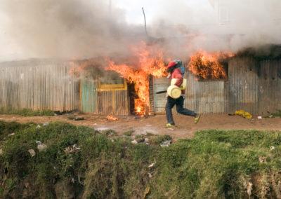 A man runs amid blazing houses in the Nairobi slum of Soweto Kibera.