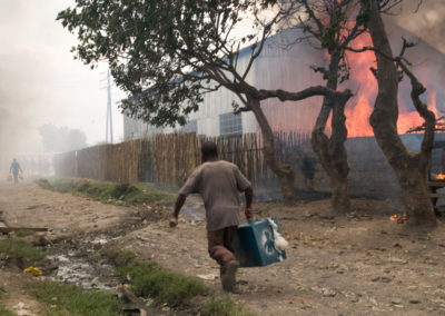 A young man runs with a suitcase from burning houses in the Naukuru slum of Idima.