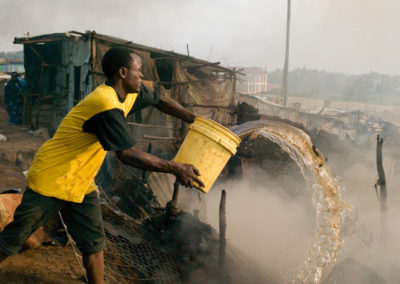 A man throws water on the smoldering remains of a house in the Nairobi slum of Soweto Kibera.