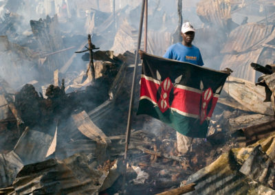 A young man salvaged an immaculate flag of Kenya while picking through the remains of a smoldering house set on fire during clashes in the Nairobi slum of Soweto Kibera.