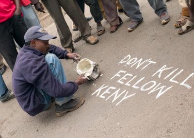 A man scrolls graffiti on the pavement in Kibera slum, Nairobi.
