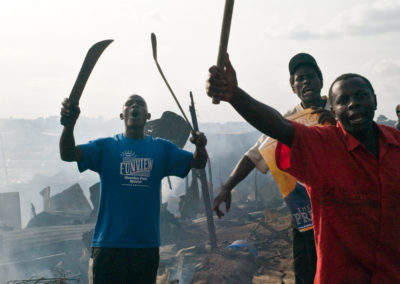 A group of Luo men express their anger at the burning houses around them in Soweto slum, Nairobi. They accused Kikuyus of the arson.