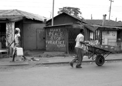 Residents of Kibera slum in Nairobi walk pas anti-violence graffiti.