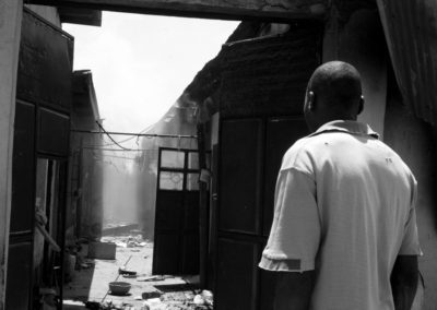 A man surveys the remains after houses were set on fire by rivalling tribe members in Nakuru.