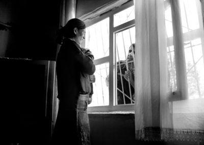 A Kurdish woman talks with her cousin through the window of her Diyarbakir in home.