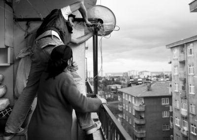 Gule Tasli helps her son install a satellite dish for the new television they just bought.
